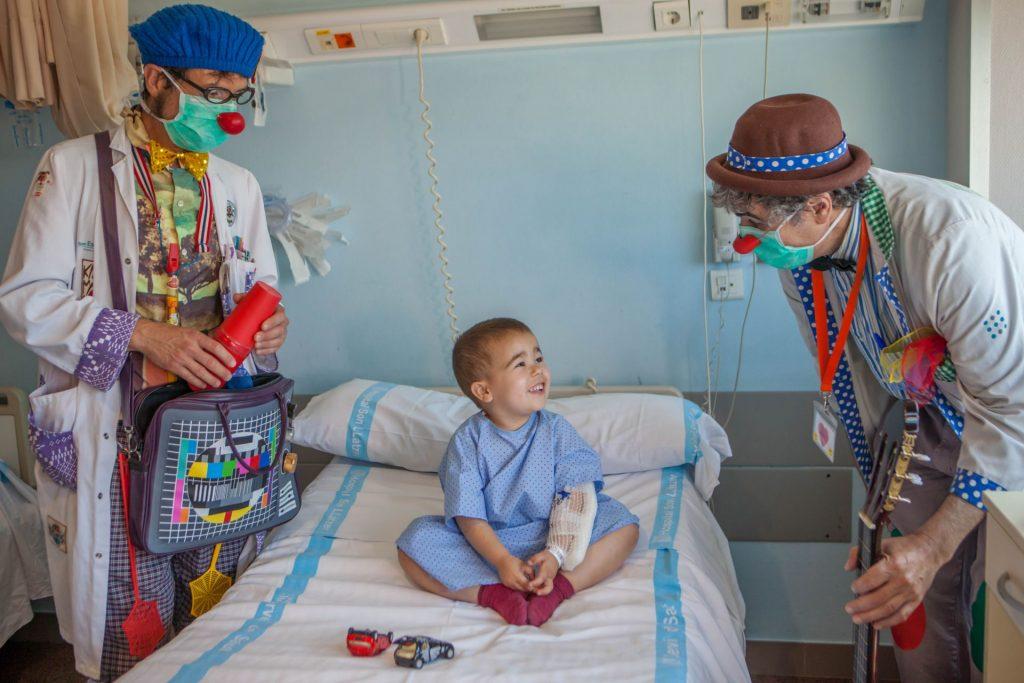 Payasos de sonrisa médica con un niño hospitalizado.